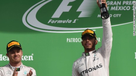 Lewis Hamilton raises the trophy after beating Mercedes teammate Nico Rosberg into second place in the Mexican Grand Prix.