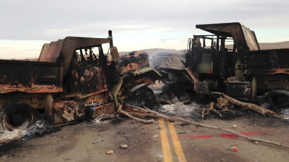 The burned hulks of heavy trucks sit on Highway 1806 on Friday, October 28, near a spot where Dakota Access Pipeline protesters were evicted a day earlier.