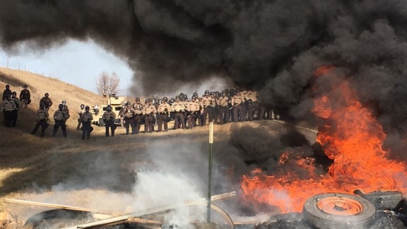 Tires burn as armed soldiers and law enforcement officers stand in formation to force Dakota Access Pipeline protesters off the private land in Morton County.