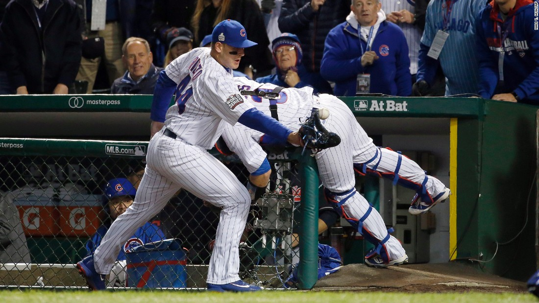 Chicago Cubs first baseman Anthony Rizzo (44) reaches for a ball bounced off from catcher David Ross who was trying to catch a foul ball hit by Cleveland's Carlos Santana during the second inning of Game 5.
