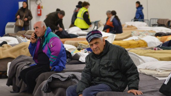 Residents prepare to spend the night in a camp set up in a warehouse in the village of Caldarola on Sunday following the quake.