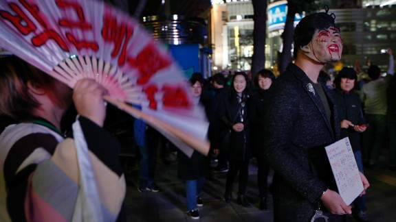"""A protester wearing a mask of Park Geun-Hye holds a placard saying """"Why do you need Halloween fest? We can see all the horror in our lives,"""" during the protest."""