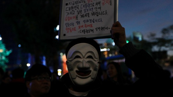 """A protester wearing a traditional Korean mask holds a placard saying """"You Need to Resign Now"""" during the protest."""