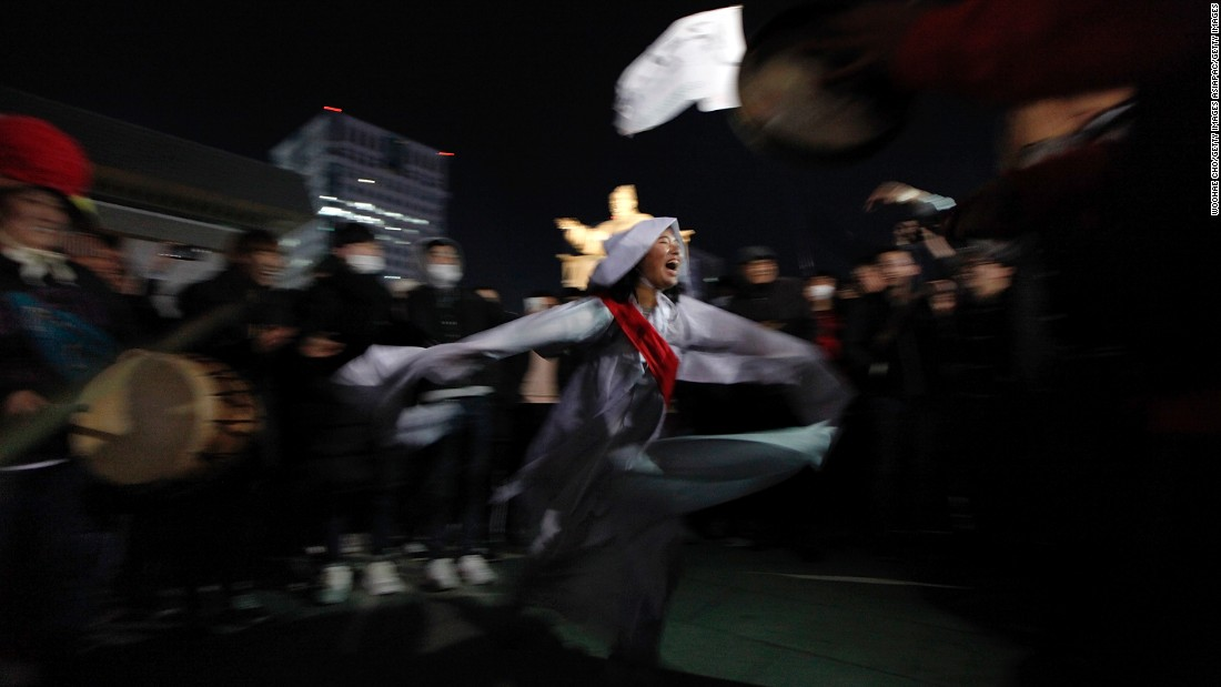 A protester satirizes President Park's relationship with Choi Soon-Sil, wearing a costume of a shaman during the Saturday night protest.