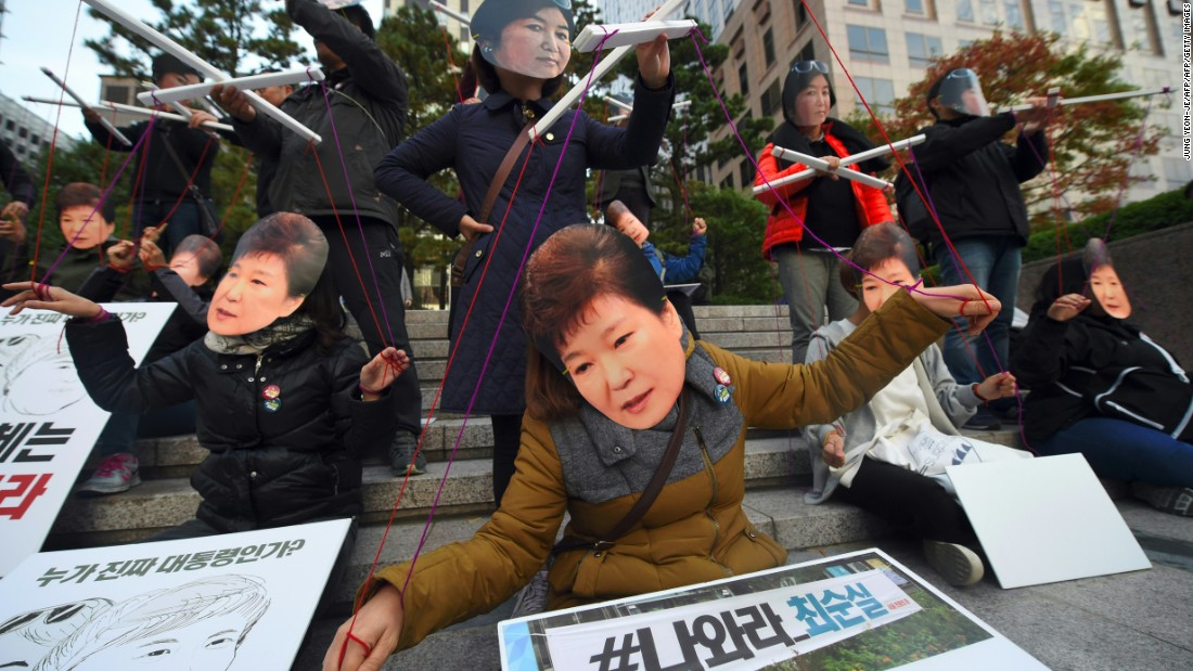 Protesters wearing masks of South Korean President Park Geun-Hye and her confidante Choi Soon-Sil perform before a candlelit rally in central Seoul on Saturday.