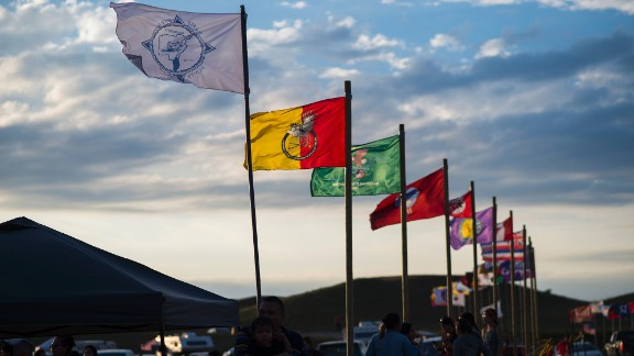 Flags of Native American tribes from across the United States and Canada line the entrance of the camp.