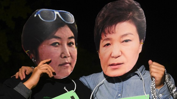 """Protestors wearing masks of South Korean President Park Geun-Hye (R) and her confidante Choi Soon-Sil (L) pose for a performance during a rally denouncing a scandal over President Park's aide in Seoul on October 27, 2016. South Korean prosecutors on October 27 set up a high-powered """"task-force"""" to probe a widening scandal involving alleged influence-peddling by a close confidante of President Park Geun-Hye. Choi Soon-Sil, an enigmatic woman with no government position, was already part of an investigation into allegations that she used her relationship with the president to strong-arm conglomerates into multi-million dollar donations to two non-profit foundations.  / AFP / JUNG YEON-JE        (Photo credit should read JUNG YEON-JE/AFP/Getty Images)"""