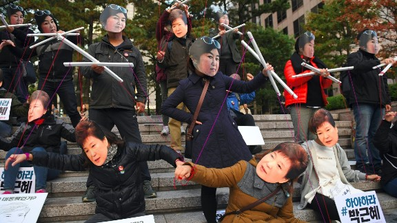 Protesters wear masks of South Korean President Park Geun-hye and Choi Soon-sil.