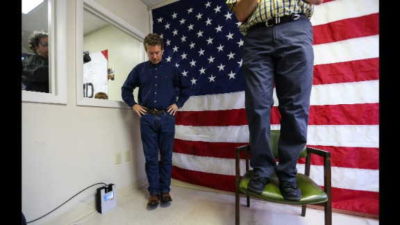 U.S. Sen. Rand Paul, a Republican presidential candidate from Kentucky, looks down as New Hampshire Sen. Andy Sanborn, standing on a chair, makes opening remarks at the opening of Paul