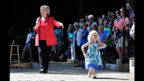 Louisa Hill, 3, walks onto a stage in Hanover, New Hampshire, as Clinton speaks on July 3, 2015.