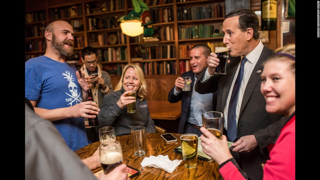Republican presidential candidate Rick Santorum, second from right, drinks a beer at a pub in Waukee, Iowa, on January 28, 2016. The former U.S. senator from Pennsylvania also ran in 2012.