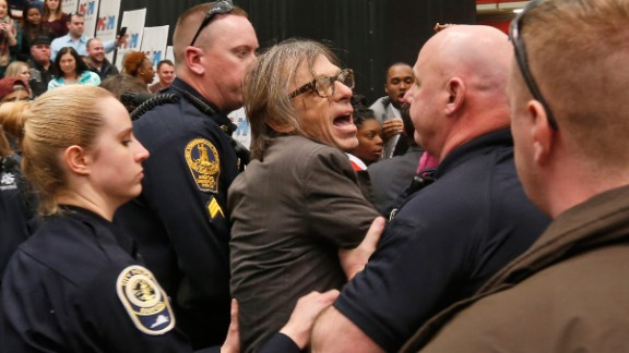 Christopher Morris, a photographer on assignment for Time magazine, is escorted by police during a Trump rally in Radford, Virginia, on February 29, 2016. Morris said a Secret Service agent choked him and slammed him to the ground as he tried to leave a media pen at the event. The incident was caught on video.