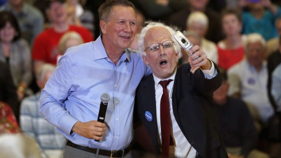 Ohio Gov. John Kasich, one of the Republican presidential candidates, poses with a Sanders impersonator at the end of a town-hall meeting in Palatine, Illinois, on March 9, 2016.