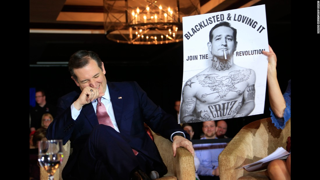 Cruz laughs at a poster while speaking a town-hall event in Madison, Wisconsin, on March 30, 2016.