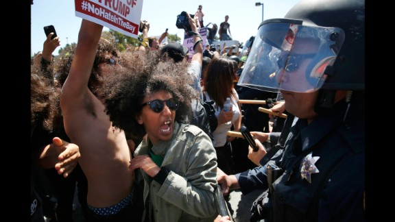 Protester Biseat Yawkal yells as she is pushed by police outside of the California Republican Convention on April 29, 2016. Trump protesters -- some of whom wore bandanas over their faces and carried Mexican flags -- blocked off the road in front of the Hyatt Regency, forcing Trump