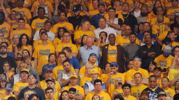 Sanders, at center in the light-blue shirt, watches a playoff basketball game in Oakland, California, on May 30, 2016. The candidate, campaigning for the state