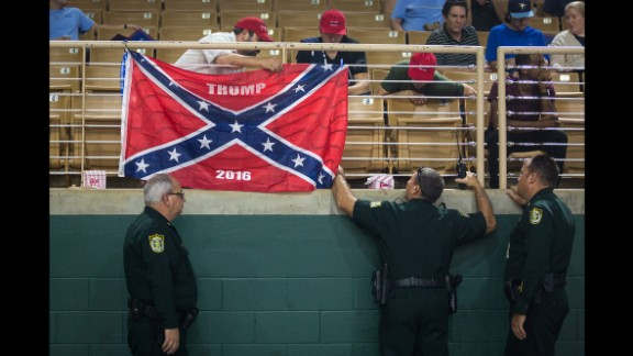Law enforcement officers make Trump supporters remove a Confederate flag display at a Trump rally in Kissimmee, Florida, on August 11, 2016.