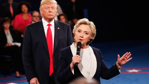 Trump looms behind Clinton at the second debate, which was a town-hall format with questions from undecided voters.