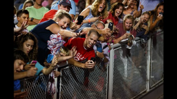 Trump supporters take photos of Trump as he leaves a rally in Mobile, Alabama, on August 21, 2015. The rally was held in a football stadium to accommodate 30,000 supporters.
