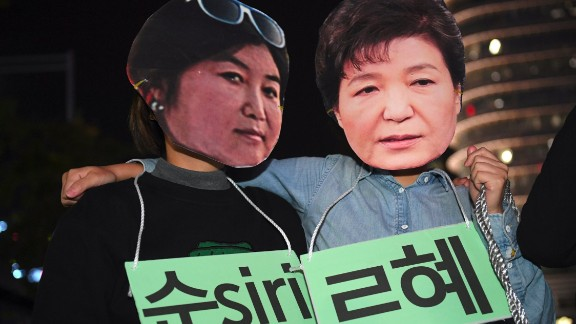"Protestors wearing masks of South Korean President Park Geun-Hye (R) and her confidante Choi Soon-Sil (L) pose for a performance during a rally denouncing a scandal over President Park's aide in Seoul on October 27, 2016. South Korean prosecutors on October 27 set up a high-powered ""task-force"" to probe a widening scandal involving alleged influence-peddling by a close confidante of President Park Geun-Hye. Choi Soon-Sil, an enigmatic woman with no government position, was already part of an investigation into allegations that she used her relationship with the president to strong-arm conglomerates into multi-million dollar donations to two non-profit foundations.  / AFP / JUNG YEON-JE        (Photo credit should read JUNG YEON-JE/AFP/Getty Images)"