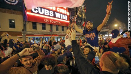 Chicago Cubs fans celebrate in front of  Wrigley Field in Chicago on Wednesday, Nov. 2, 2016, after the Cubs beat the Cleveland Indians 8-7 in Game 7 of the Major League World Series in Cleveland. (AP Photo/Charles Rex Arbogast)