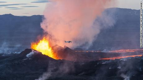An aerial picture taken on September 14, 2014 shows a plane flying over the Bardarbunga volcano spewing lava and smoke in southeast Iceland.