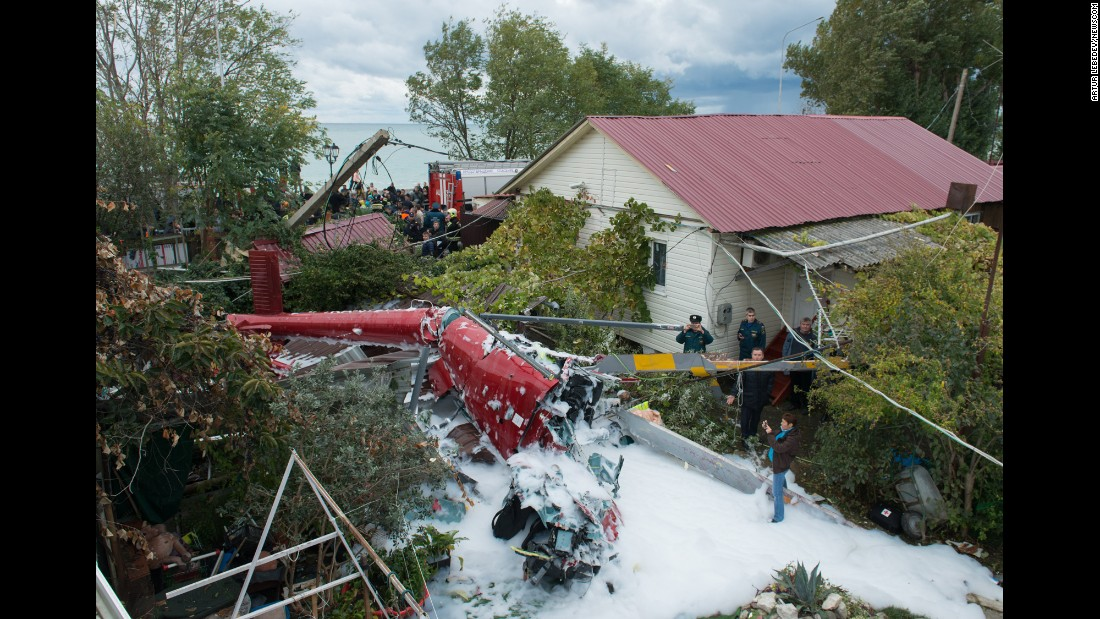Emergency personnel work at the scene of a helicopter crash in Sochi, Russia, on Tuesday, November 1. At least one person was killed and several were injured after the aircraft crashed into a house.