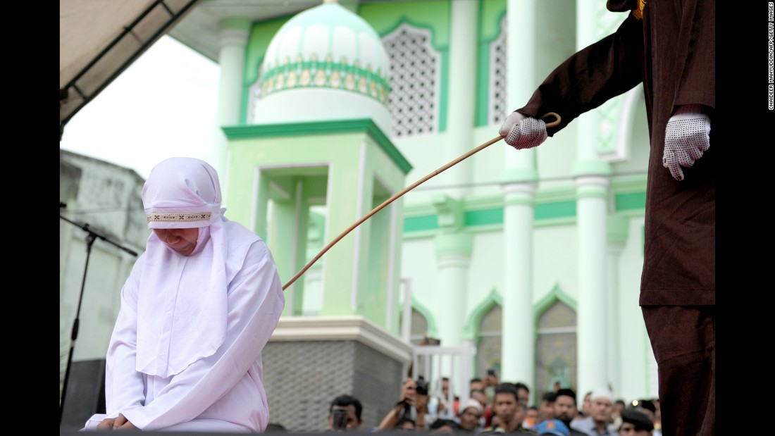 A woman is caned in Banda Aceh, Indonesia, on Monday, October 31. The province of Aceh is strictly Muslim and is the only province in the country implementing Sharia law. Public canings happen there regularly and often attract huge crowds.