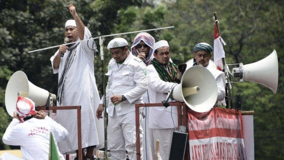 Muslim leaders broadcast their message as they march past Jakarta