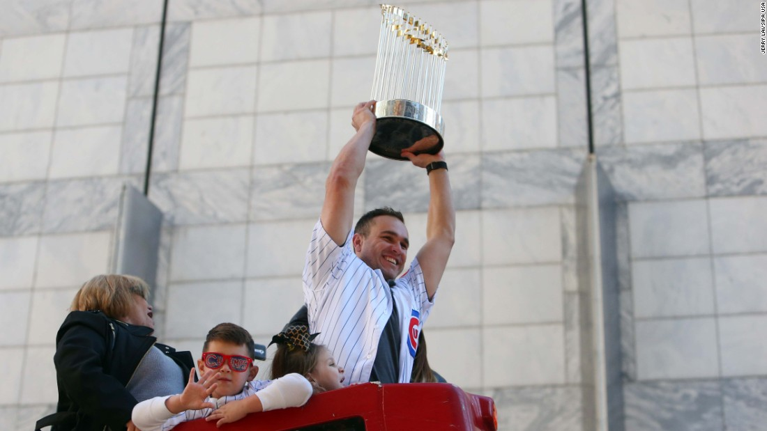 Cubs catcher Miguel Montero hoists the championship trophy during the parade.