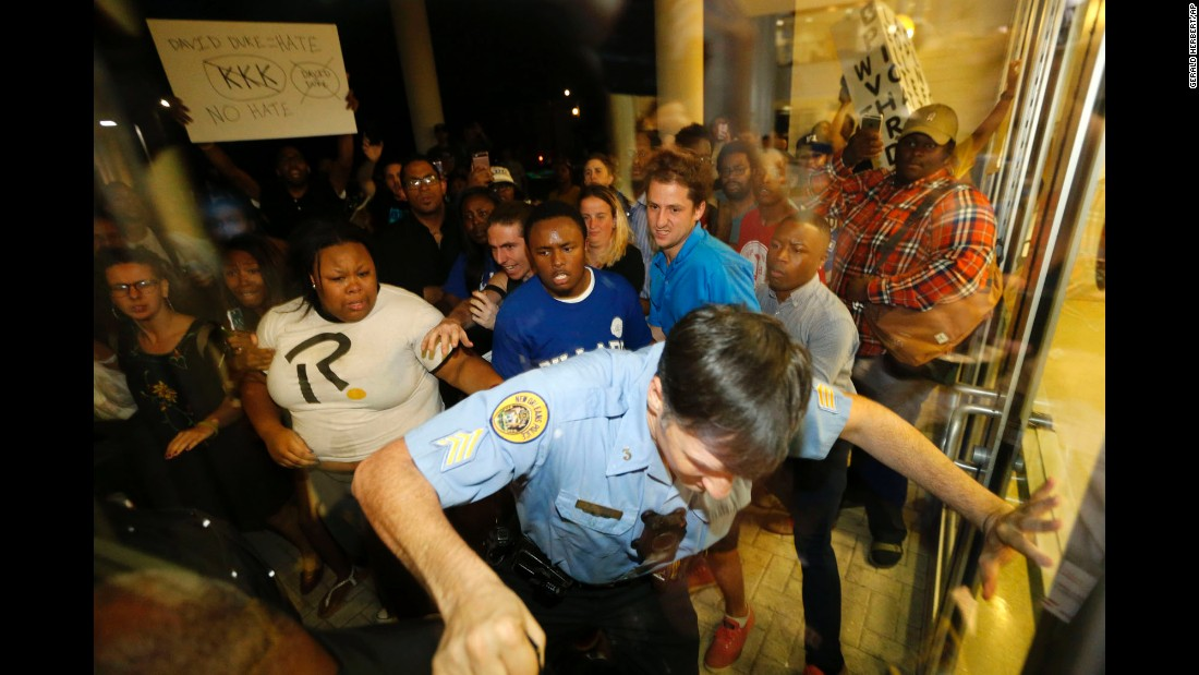"A police officer in New Orleans tries to keep protesters outside a debate venue at Dillard University on Wednesday, November 2. People <a href=""http://www.cnn.com/2016/11/02/politics/david-duke-kkk-protesters-louisiana-senate/"" target=""_blank"">were protesting David Duke,</a> a Senate candidate and former Ku Klux Klan leader who was participating in the debate at the historically black college."