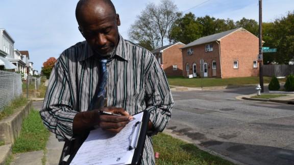 Muhammad As-saddique Abdul-Rahman writes down a resident's email address in the Blackwell neighborhood of Richmond, Virginia, on October 30, 2016.