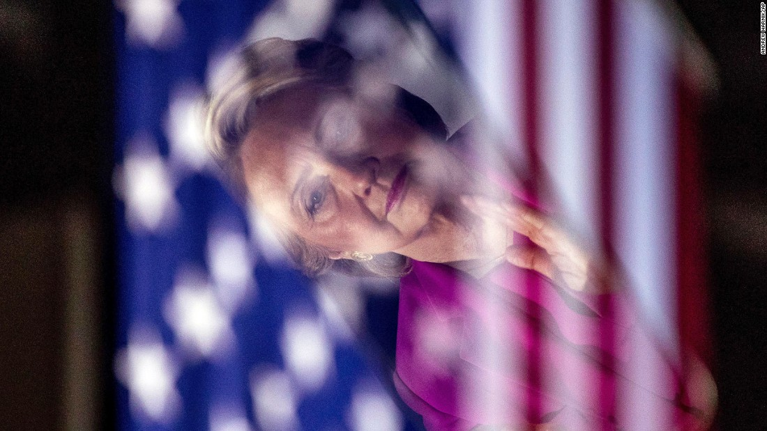 Clinton, seen in a reflection, applauds as her former primary rival, U.S. Sen. Bernie Sanders, campaigns for her in Raleigh, North Carolina, on Thursday, November 3.