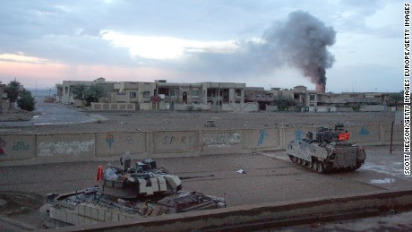 US Bradley fighting vehicles hold a position inside a schoolyard during heavy fighting in Falluja in 2004
