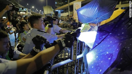 Protesters use umbrellas to block the pepper spray from police officers.