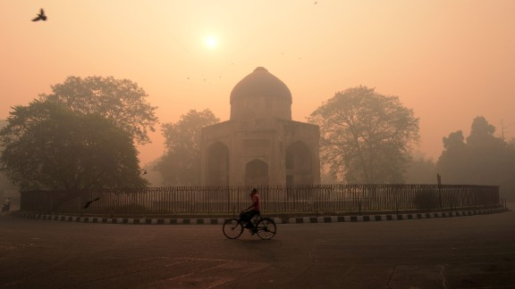 An Indian cyclist rides along a street as smog envelops a monument in New Delhi on October 31, the day after the Diwali festival.