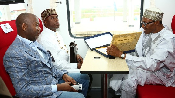 Nigerian President Mohammadu Buhari (right) signs visitor