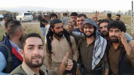 Kurdish soldier Ako Abdourahman, pictured center,  has rescued dozens of people in Kirkuk, Iraq, driving to residents houses and retrieving them in his bulletproof BMW.