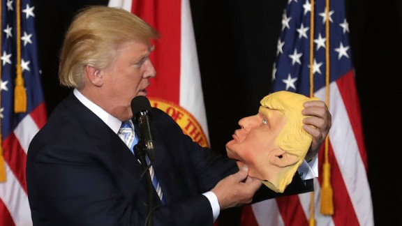 Trump checks out a rubber mask of himself during a campaign rally in Sarasota, Florida, on November 7.