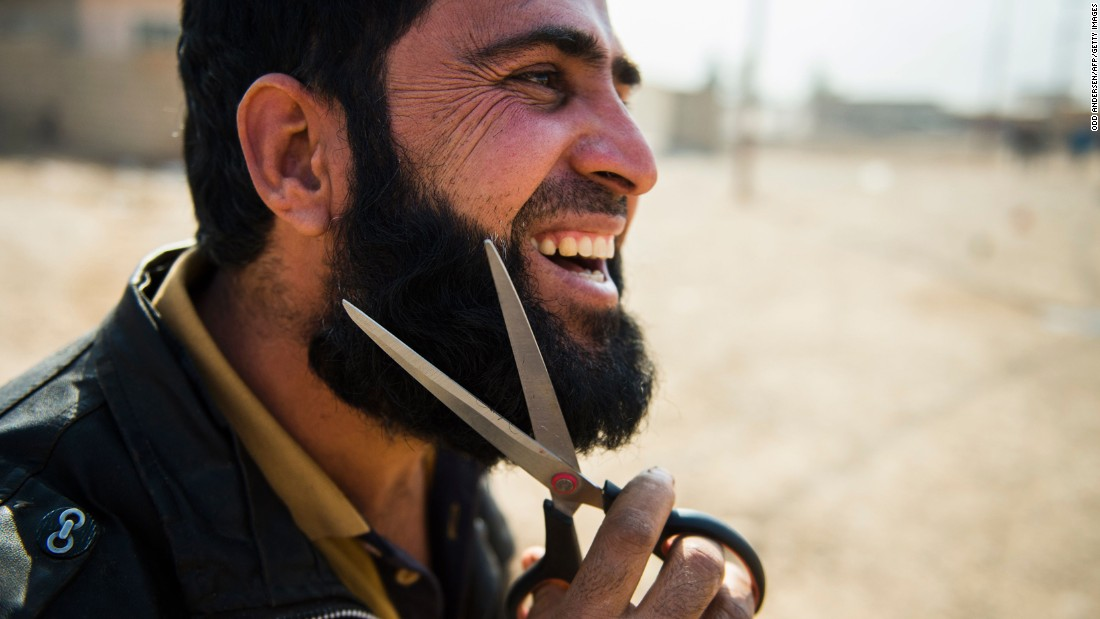 A civilian man who fled the fighting trims his beard after reaching an Iraqi army position in Mosul on November 7.