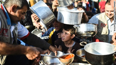 Displaced Iraqi boys wait to receive food at a refugee camp outside of Mosul.