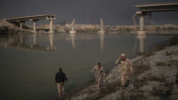 Iraqi soldiers pass near a bridge destroyed in an airstrike in Qayyara on November 5.