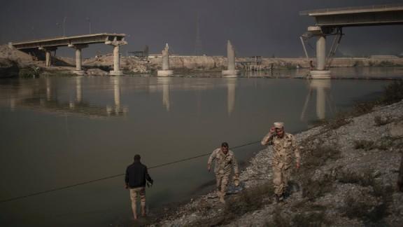 Iraqi soldiers pass near a bridge destroyed in an airstrike in Qayyara on November 5.