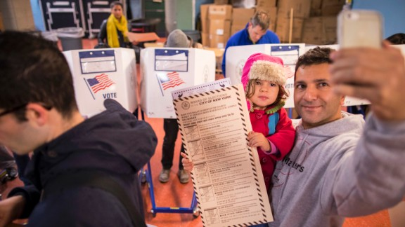 A man snaps a selfie with his child as he waits to vote in Brooklyn, New York.