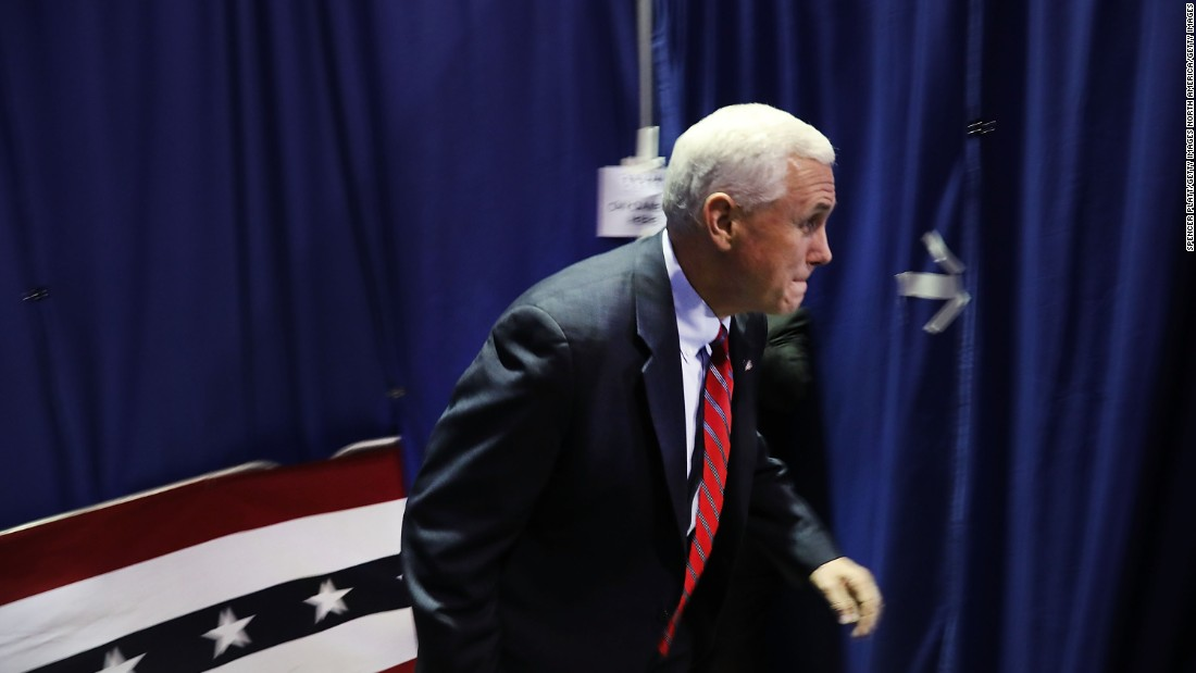 Pence runs onto the stage at a rally on October 25, 2016, in Marietta, Ohio.