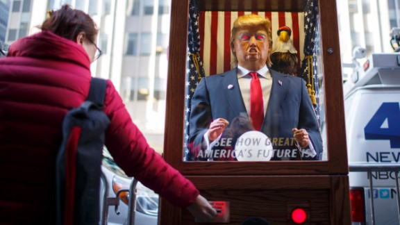 "A tourist takes her ""misfortune"" slip from The All-Seeing Trump, a machine set up across the street from the New York Hilton Midtown Manhattan Hotel."