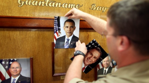 GUANTANAMO BAY, CUBA - JANUARY 20:  (NOTE TO EDITORS: PHOTO HAS BEEN REVIEWED BY US MILITARY OFFICIALS) U.S. Navy Chief Petty Officer Bill Mesta replaces an official picture of outgoing President George W. Bush with that of newly- sworn-in U.S. President Barack Obama, in the lobby of the headquarters of the U.S. Naval Base January 20, 2009 in Guantanamo Bay, Cuba.  Bush