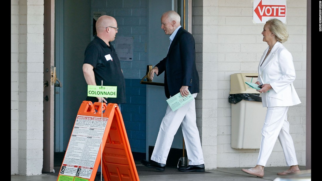U.S. Sen. John McCain and his wife, Cindy, arrive at a polling place to cast their votes in Phoenix.