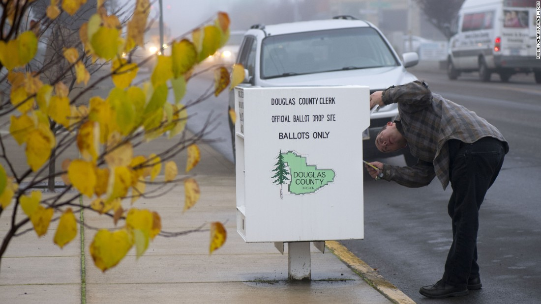 A voter drops his ballot into a voting box in Sutherlin, Oregon.