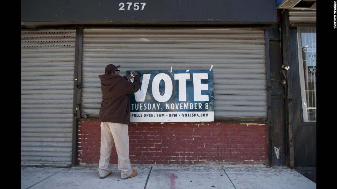 A man in Philadelphia hangs a sign reminding people to vote.